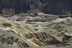 De verre bergweg, de kromming van de grijze asfaltband onder de ruwe gele rotsen, de donkere achtergrond Royalty-vrije Stock Afbeeldingen