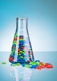 De verre complètement des pilules et des comprimés de couleur sur le plancher Images stock