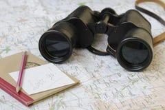 De verrekijkers en het notitieboekje zijn op de toeristenkaart stock foto's