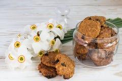 De vers gebakken koekjes en de narcissen van de havermeelrozijn Stock Afbeelding