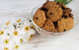 De vers gebakken koekjes en de narcissen van de havermeelrozijn Royalty-vrije Stock Afbeeldingen