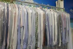 De vers schoongemaakte overhemden van mensen en damesblouses in het textiel schoonmaken stock foto's