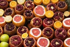 De verscheidenheid van rijpe sappige vruchten, gepelde granaatappel, sneed sinaasappel en grapefruit en groene appelen royalty-vrije stock fotografie