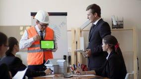 De verschijning van ingenieursAsian met een helm en een helder vest, toont het plan van de tabletbouw op lijst de lay-out is stock footage
