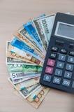 De verschillende bankbiljetten van verschillende benamingen worden gestapeld in een ventilator en een calculator Stock Foto