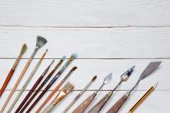De verschillende borstels aan verf op een witte houten achtergrond, bovenkant wedijveren Stock Afbeelding