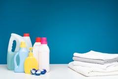 De verschillende flessen detergentia zetten samen met handdoeken aan Stock Afbeeldingen