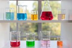 De verschillende grootte van laboratoriumglaswerk op de witte plank royalty-vrije stock afbeelding