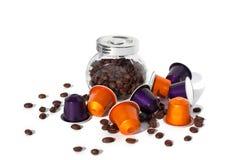 De verschillende kleuren van koffiecapsules en glaskruik met koffiebonen op witte geïsoleerde achtergrond stock fotografie