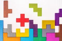 De verschillende kleurrijke vormen houten blokken op beige vlakke achtergrond, leggen Geometrische vormen in verschillende kleure Royalty-vrije Stock Afbeelding