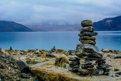 De verschillende met maat rotsen stapelden en brachten op een andere bij de kust van een mooie overzees in evenwicht royalty-vrije stock foto's