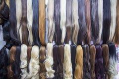 De verschillende uitbreidingen van het kleuren menselijke haar in pruikenwinkel stock foto