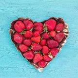 De verse aardbeien in hartvorm plateren op blauwe houten lijst, exemplaarruimte Het hart van de aardbei Stock Foto's