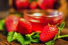 De verse aardbeien met bladeren en de jam sluiten Stock Foto