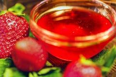 De verse aardbeien met bladeren en de jam sluiten Royalty-vrije Stock Afbeelding