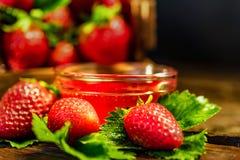 De verse aardbeien met bladeren en de jam sluiten Royalty-vrije Stock Foto's