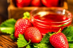 De verse aardbeien met bladeren en de jam sluiten Stock Afbeeldingen