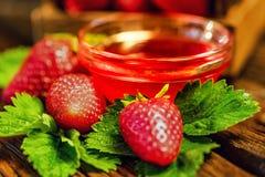 De verse aardbeien met bladeren en de jam sluiten Royalty-vrije Stock Afbeeldingen