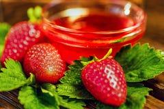 De verse aardbeien met bladeren en de jam sluiten Stock Foto's