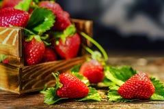 De verse aardbeien met bladeren in houten doos sluiten Royalty-vrije Stock Foto's