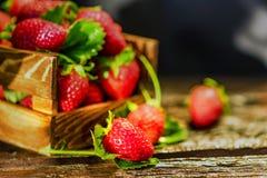 De verse aardbeien met bladeren in houten doos sluiten Stock Fotografie