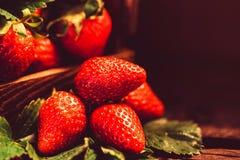 De verse aardbeien met bladeren in houten doos sluiten Royalty-vrije Stock Afbeeldingen