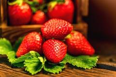 De verse aardbeien met bladeren in houten doos sluiten Royalty-vrije Stock Foto
