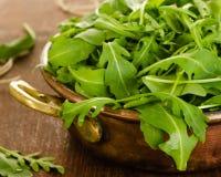 De verse bladeren van de rucolasalade in kom Stock Afbeelding