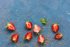 De verse die aardbeienhelften met geraspte chocolade op een blauwe achtergrond worden bestrooid Hoogste mening, exemplaarruimte Stock Foto