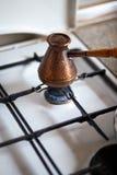 De verse die koffie met kardemom kookte in cezve - Koffie in een koper cezve op een gasfornuis in comfortabele typische keuken bi royalty-vrije stock afbeeldingen