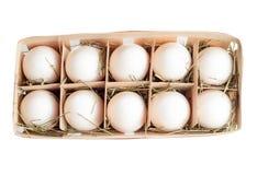 De verse eieren worden ingepakt in een mand op hooi Stock Foto
