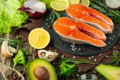 De verse forel van het vissenlapje vlees, zalm, zalm, rood visvlees Met ingrediënten en groenten op een houten achtergrond, vlak- stock afbeelding