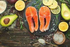 De verse forel van het vissenlapje vlees, zalm, zalm, rood visvlees Met ingrediënten en groenten op een houten achtergrond, vlak- royalty-vrije stock foto's
