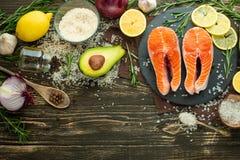 De verse forel van het vissenlapje vlees, zalm, zalm, rood visvlees Met ingrediënten en groenten op een houten achtergrond, vlak- stock foto's