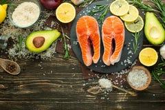 De verse forel van het vissenlapje vlees, zalm, zalm, rood visvlees Met ingrediënten en groenten op een houten achtergrond, vlak- stock foto