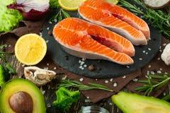 De verse forel van het vissenlapje vlees, zalm, zalm, rood visvlees Met ingrediënten en groenten op een houten achtergrond, vlak- royalty-vrije stock foto