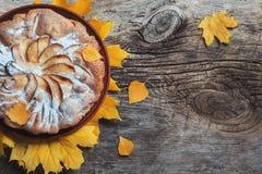 De verse gebakjeappeltaart Charlotte op houten die lijstachtergrond met de gele herfst wordt verfraaid gaat weg Dalingsvoedsel Co stock foto