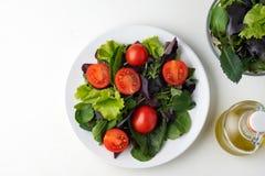 de verse gekleurde salade van de kersentomaat met arugula, Basilicum, spinazie, salade en olijfolievulling Selectieve nadruk stock afbeelding