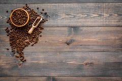De verse geroosterde koffiebonen in kom en lepel op de donkere houten mening van de lijstbovenkant kopiëren ruimte Klaar voor geb Royalty-vrije Stock Foto