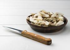 De verse gesneden paddestoelen in een klei werpen en mes op een witte houten lijst Stock Afbeeldingen