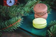 De verse groene en bruine die makarons op Kerstmislijst met spar wordt verfraaid vertakt zich met een klok Kopieer de plaats Stock Fotografie
