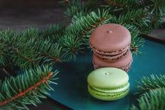 De verse groene en bruine die makaronsmakarons op Kerstmislijst met spar wordt verfraaid vertakt zich Kopieer de plaats Royalty-vrije Stock Foto
