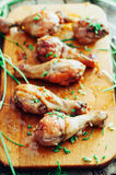 De verse heerlijke gebraden kippenbenen op een houten hakbord verfraaiden met vers bieslook Gebakken Ham Geroosterde kippenbenen  Stock Afbeelding