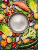 De verse kleurrijke organische ingrediënten van seizoengroenten rond leeg staal plateren op rustieke houten achtergrond, hoogste  Royalty-vrije Stock Afbeelding