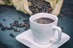 De verse koffie die met chocolade bestrooit en koffiebonen wordt verfraaid op de achtergrond stock foto