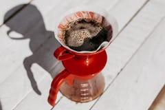 De verse koffie die van de ochtendfilter in dripper bloeien royalty-vrije stock afbeelding