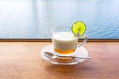 De verse melk van de citroenyoghurt in een duidelijk die glas op een bruine houten lijst met de achtergrond van de zeewateropperv stock afbeelding
