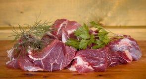 De verse ongekookte plakken van het rundvleesvlees over houten scherpe klaar raad Stock Afbeelding