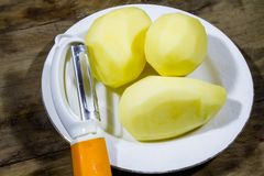 De verse oogst, gepelde aardappelknollen op een wit plateert en plantaardige snijder stock fotografie