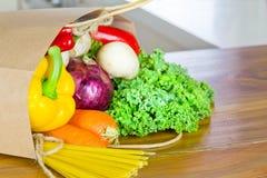 De verse Organische levering van het Rauwe groentenvoedsel in document zak op houten bank Stock Afbeelding